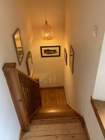 stairs with pictures and a hanging light